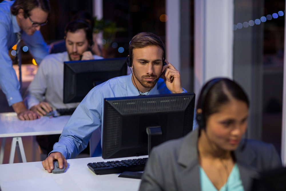 Businessman with headsets using computer in office at night.jpeg