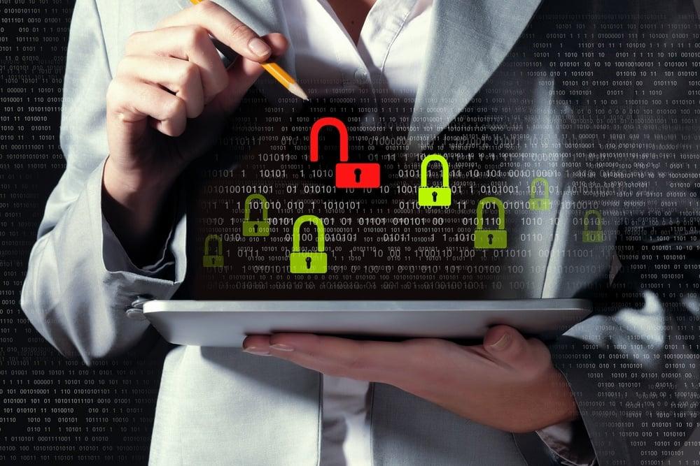 Businesswoman holding tablet pc entering password. Security concept.jpeg