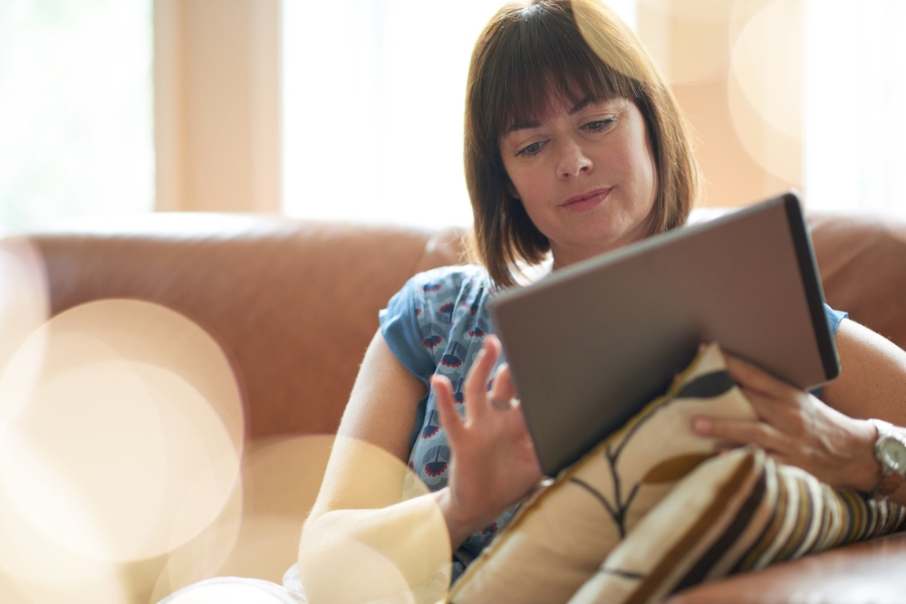 Mature woman browsing the internet on a digital tablet