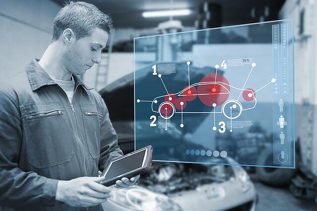 Mechanic using tablet and futuristic interface with diagram  in black and white.jpeg