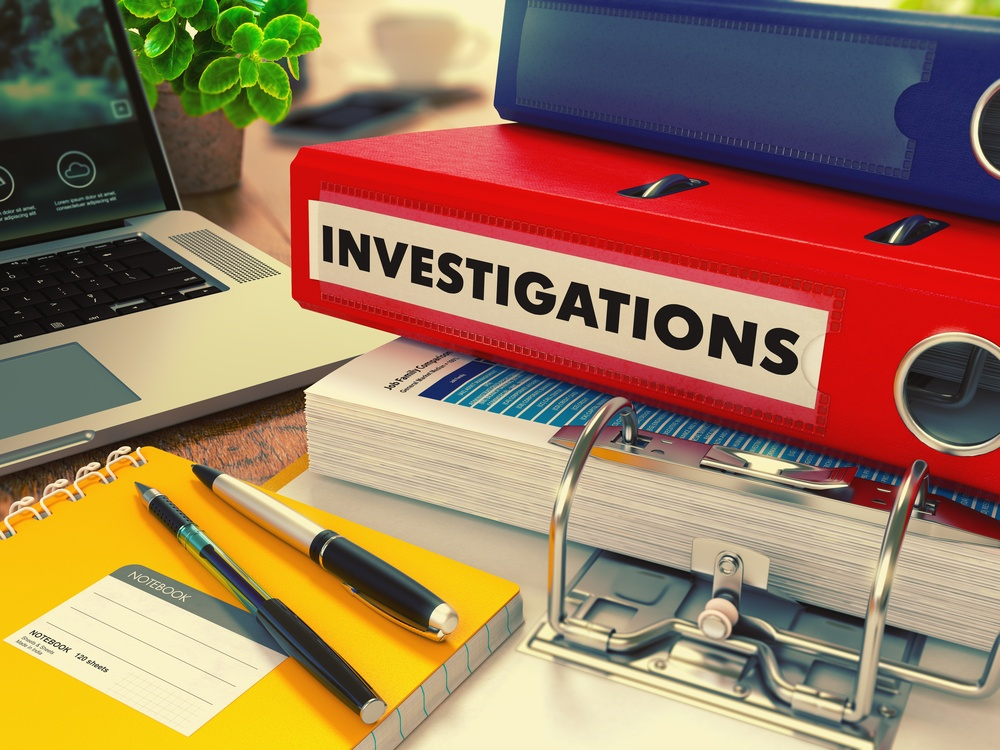 Red Office Folder with Inscription Investigations on Office Desktop with Office Supplies and Modern Laptop. Business Concept on Blurred Background. Toned Image..jpeg