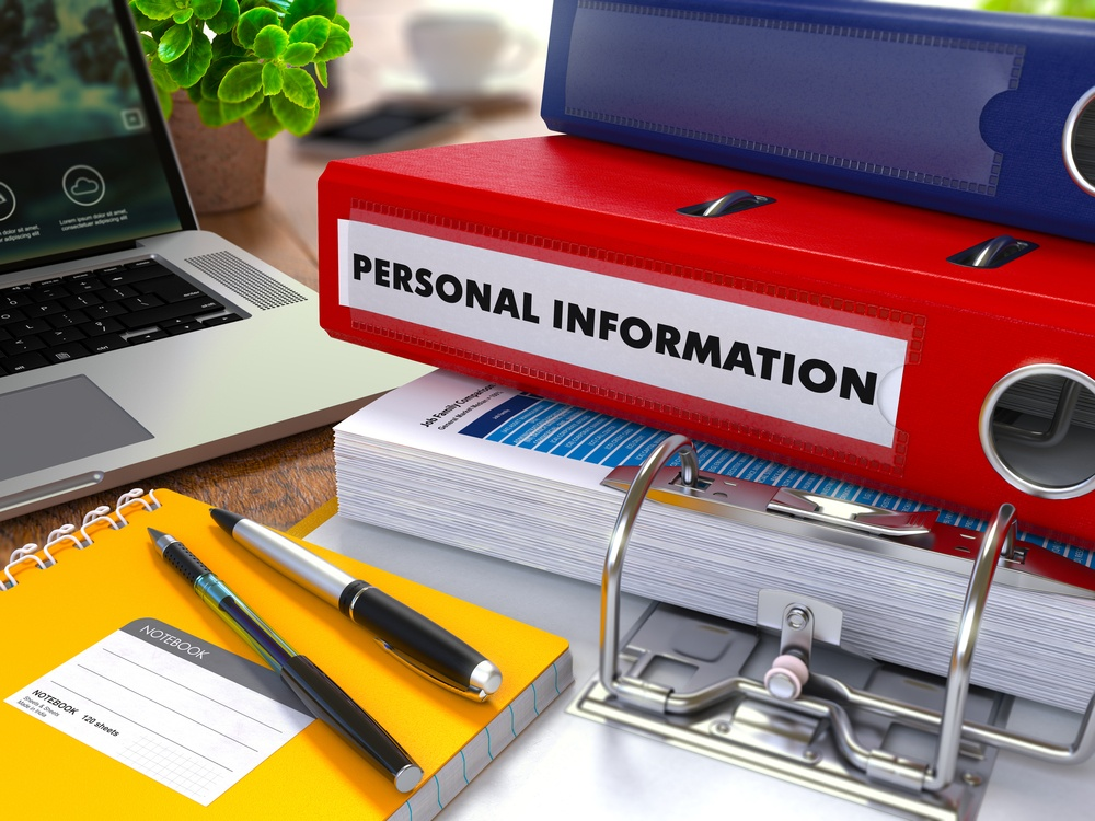 Red Ring Binder with Inscription Personal Information on Background of Working Table with Office Supplies, Laptop, Reports. Toned Illustration. Business Concept on Blurred Background..jpeg