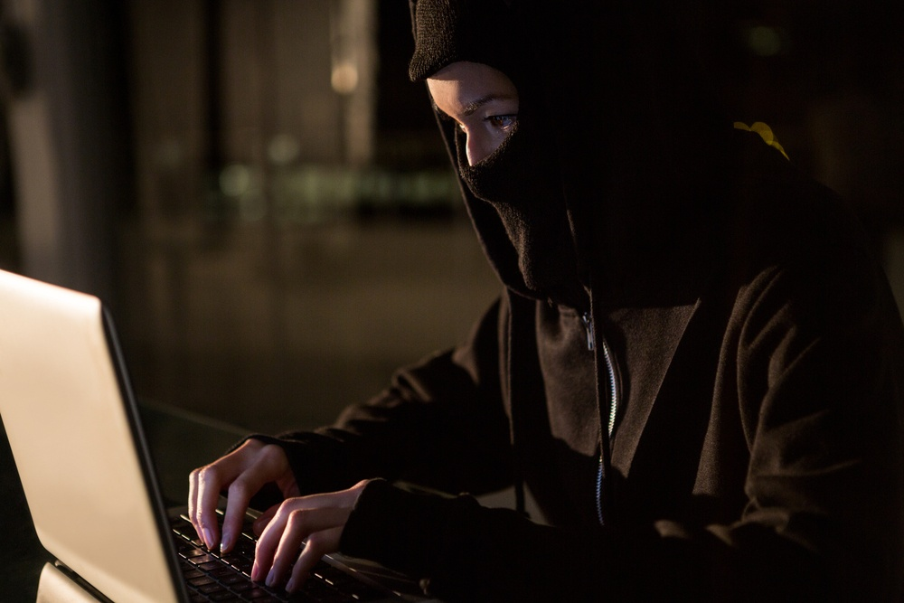Woman in balaclava using laptop in the office.jpeg