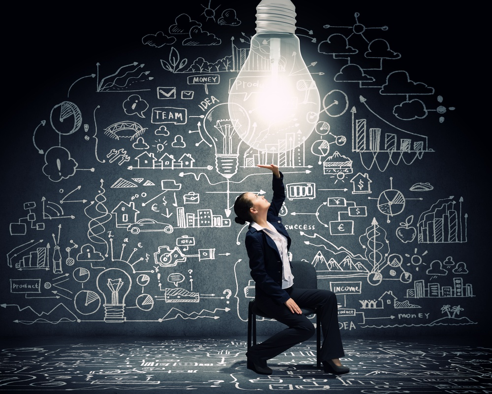 Young businesswoman sitting on chair with big light bulb above
