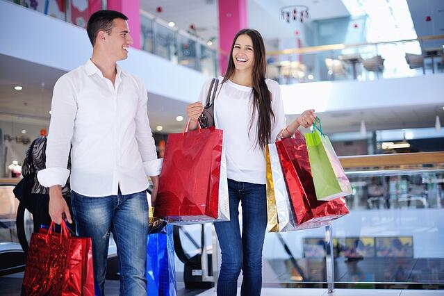 happy young couple with bags in shopping centre mall.jpeg